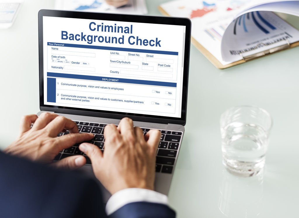 A person is sitting at their computer typing in background investigation requests.